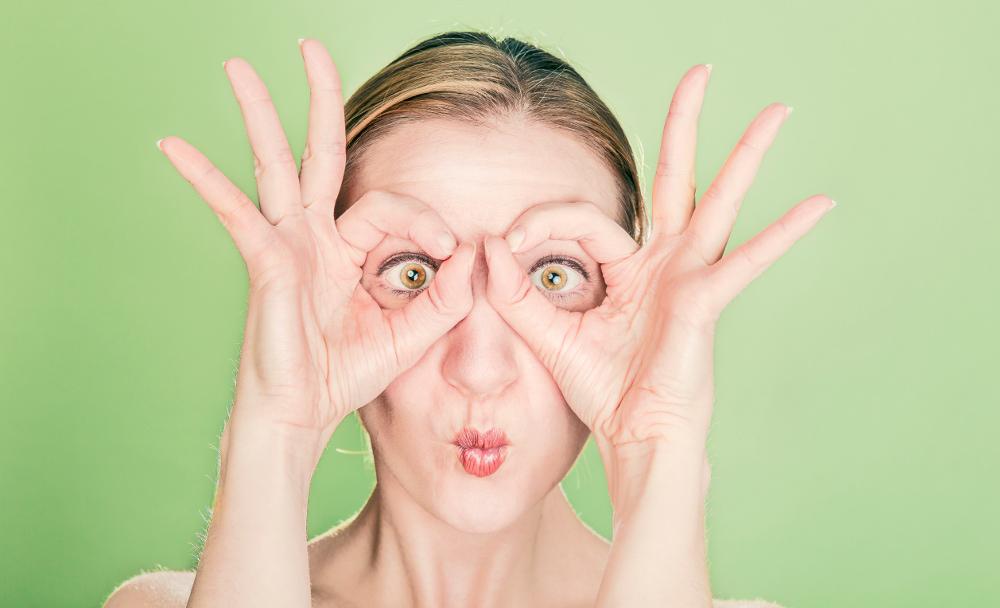 Frau macht eine Brille mit Fingern
